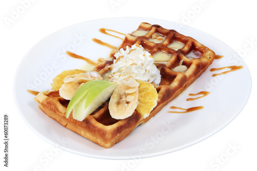 Belgian waffle with condensed milk, whipped cream and fruit.