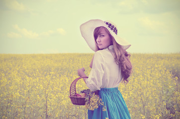 Young woman with basket at canola field