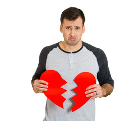 young upset sad confused man, holding red broken heart