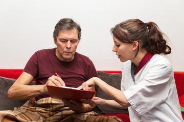 Pflegerin mit Senior im Wohnzimmer