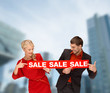 smiling woman and man with red sale sign
