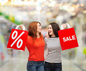 two smiling teenage girl with shopping bags