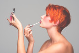 a young red-haired girl putting on makeup