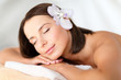 beautiful woman with flower in her hair in spa