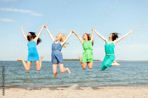 smiling girls jumping on the beach