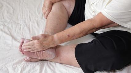 Senior woman applying cream on foot