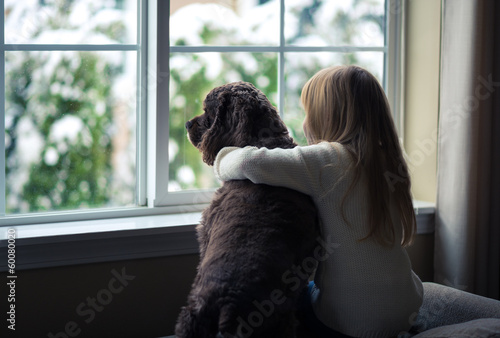 Fototapeta Little girl and her dog looking out the window.