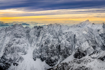 Scenic view of white winter mountains with colorful sunset