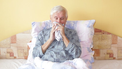 Sick senior man coughing and blowing nose in bed.