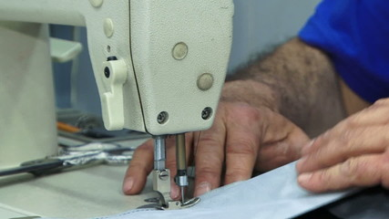 Machinist sewing lining of a car. Close-up