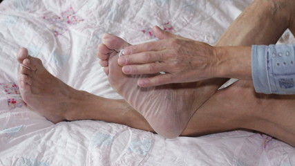 Senior applying cream on foot