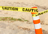 Construction site sign, yellow caution ribbon in sand