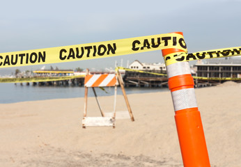 Beach construction site, yellow caution ribbon, orange pole