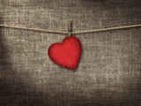 Valentine card heart shaped from old red paperr hanging on a clo