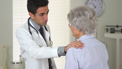 Mexican doctor talking to senior patient