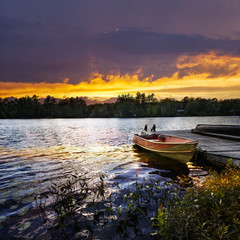 Boat docked on lake at sunset