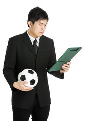Businessman looking at file pad and holding soccer ball