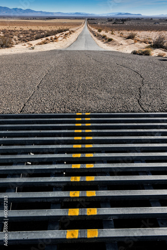 Cattle grate crossing in a road to mountains
