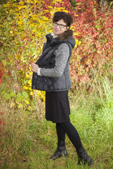 Woman in front of autumnal flowering bush