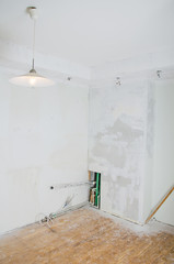 Room renovation. Gypsum plasterboard with undone socket bulbs.