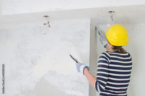 Female plasterer repairs wall. Space for your text.