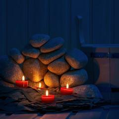 Candles are lit on the background of the sauna stones. Preparing