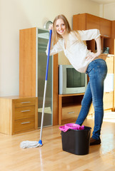 cheerful long-haired girl washing floor with mop