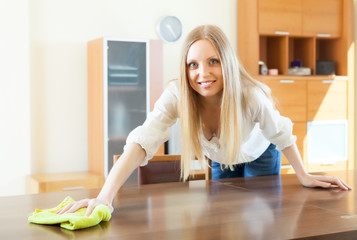 Cheerful blonde long-haired woman wiping the dust