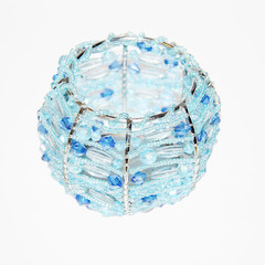 Emptyspherical candlestick with blue beads on a white background