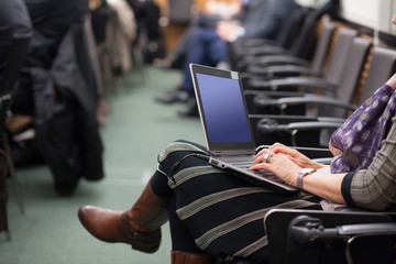 woman typing on laptop at conference