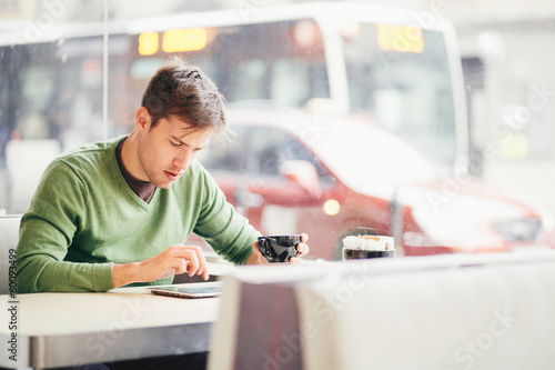 Student using tablet computer in cafe