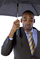 sad young black businessman holding an umbrella