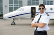Pilot With Arms Crossed Standing In Front Of Private Jet - 60097460