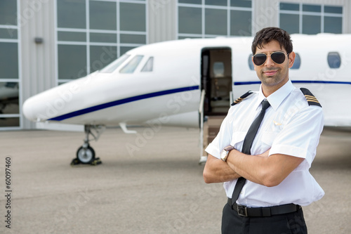 Foto Spatwand Luchthaven Pilot With Arms Crossed Standing In Front Of Private Jet