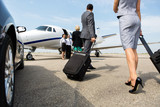 Fototapety Business Partners Walking Towards Private Jet