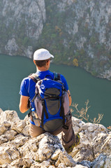 Hiker with a backpack taking a rest at cliff over Danube river