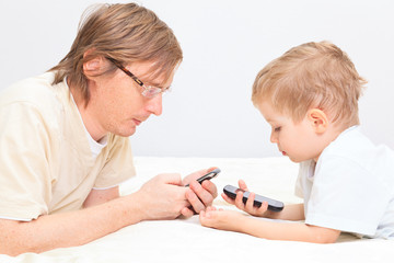father and son with mobile phones at home