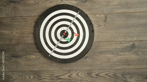 hand throwing darts at a target