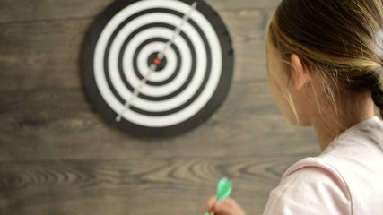 little girl throwing darts at the target