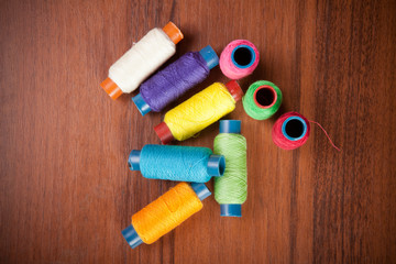 colorful spools of thread on a wooden background
