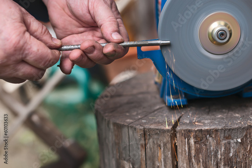 Sharpening  of iron by abrasive disk machine. Male hands sharpen
