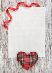 Valentine card with textile heart on old wood