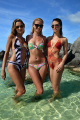 Models posing standing in shallow water of tropical ocean