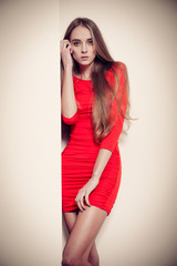 Sexy fashion woman in red dress posing near the wall