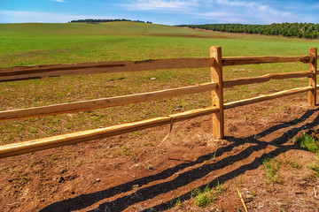 old wood fence with a green field