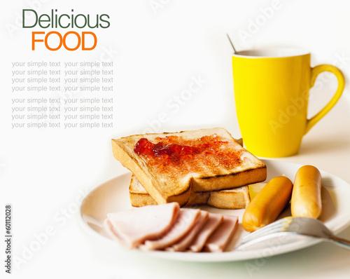 Breakfast consisting of toast, jam, bread,ham, coffee.