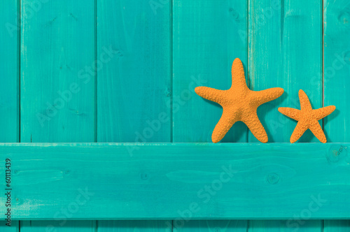 Two orange starfish against a turquoise colored wood background