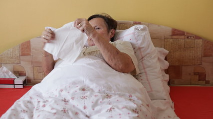 Ill senior woman blowing nose in bed.