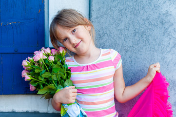 Beautiful little girl with pink roses, outdoor portrait