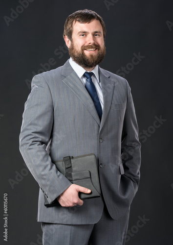 Businessman holding tablet pc on a gray background